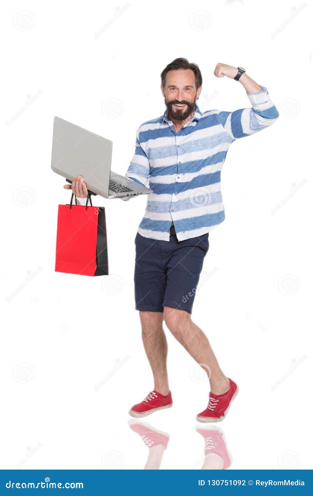 Homem farpado feliz que mostra seus músculos ao estar com portátil