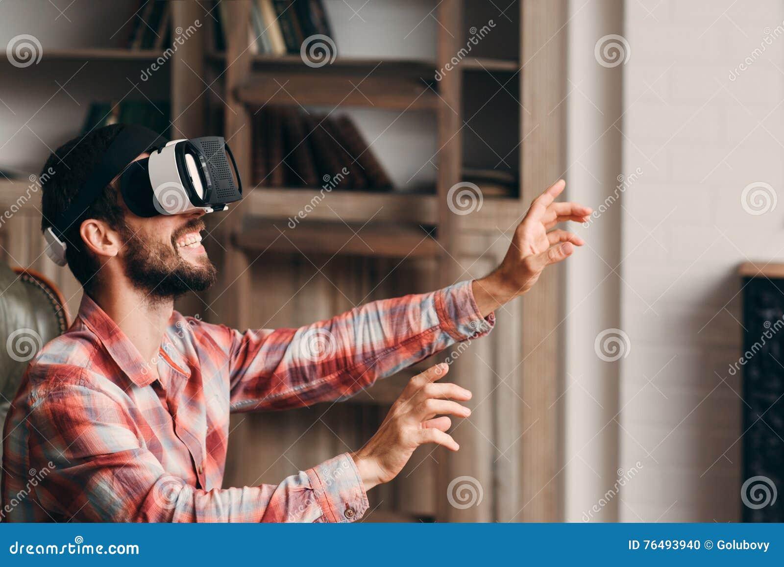 Homem farpado feliz que usa vidros do vr