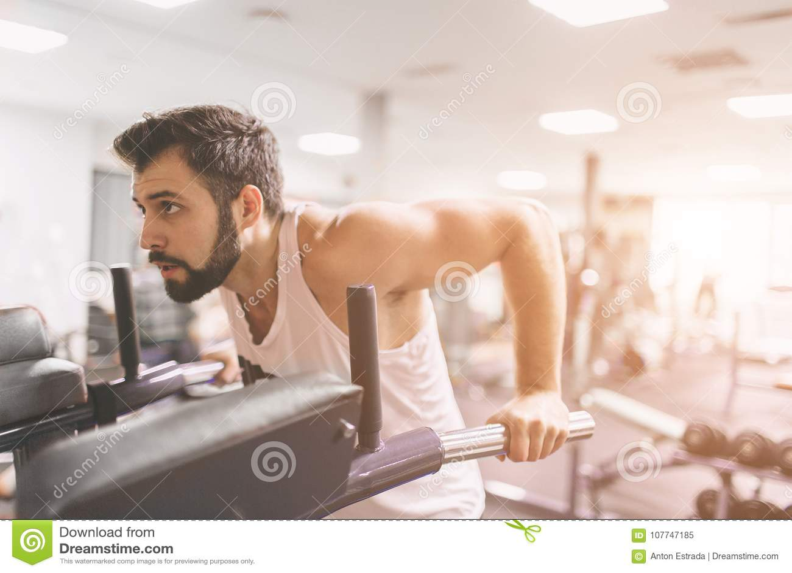 Homem farpado muscular durante o exercício no gym Um retrato de um modelo masculino atlético focalizado na roupa branca que faz m