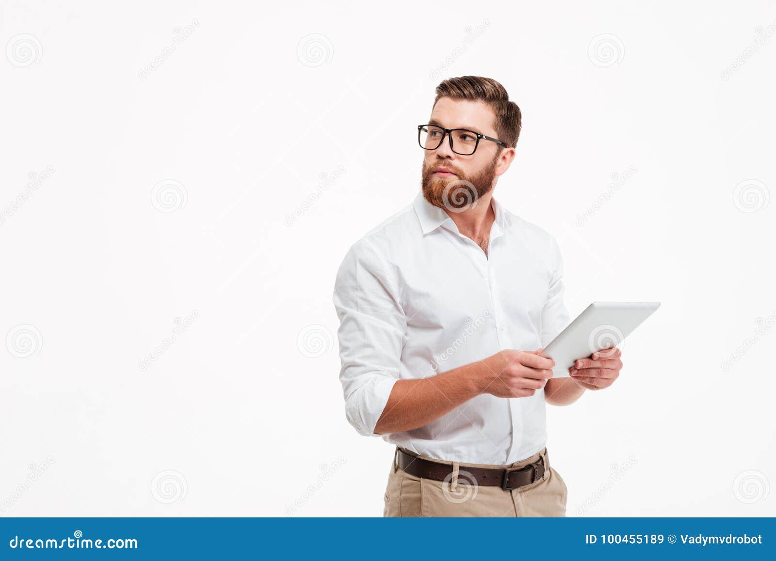 Homem farpado novo sério que usa o tablet pc