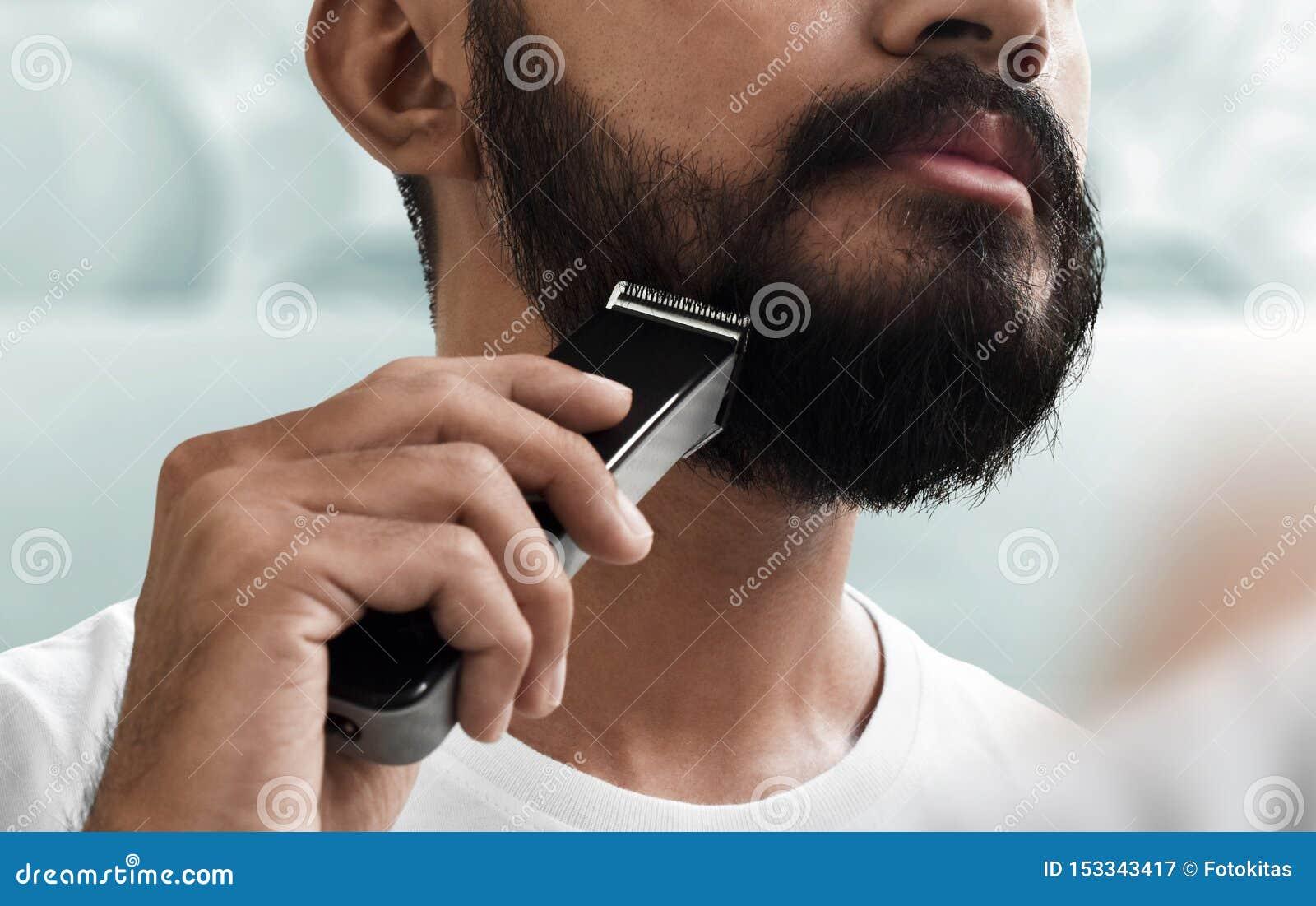 Homem farpado que barbeia sua barba