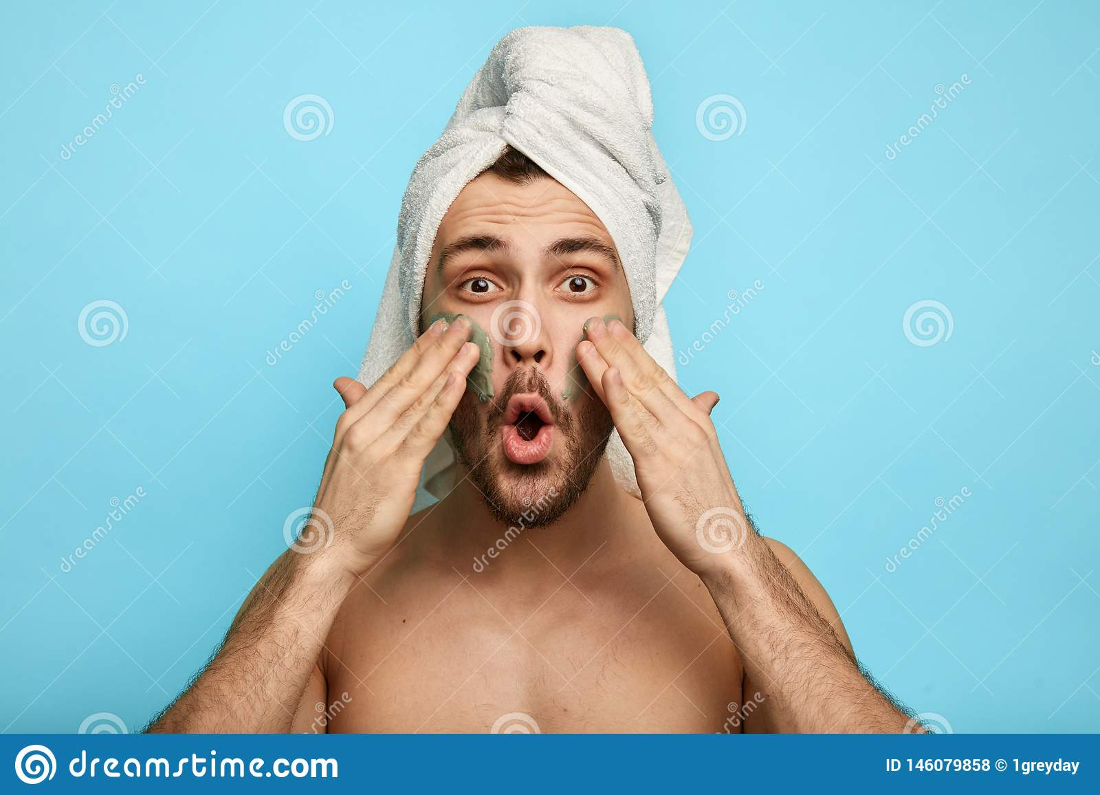 Homem farpado relaxado que aplica uma máscara em seu mordente