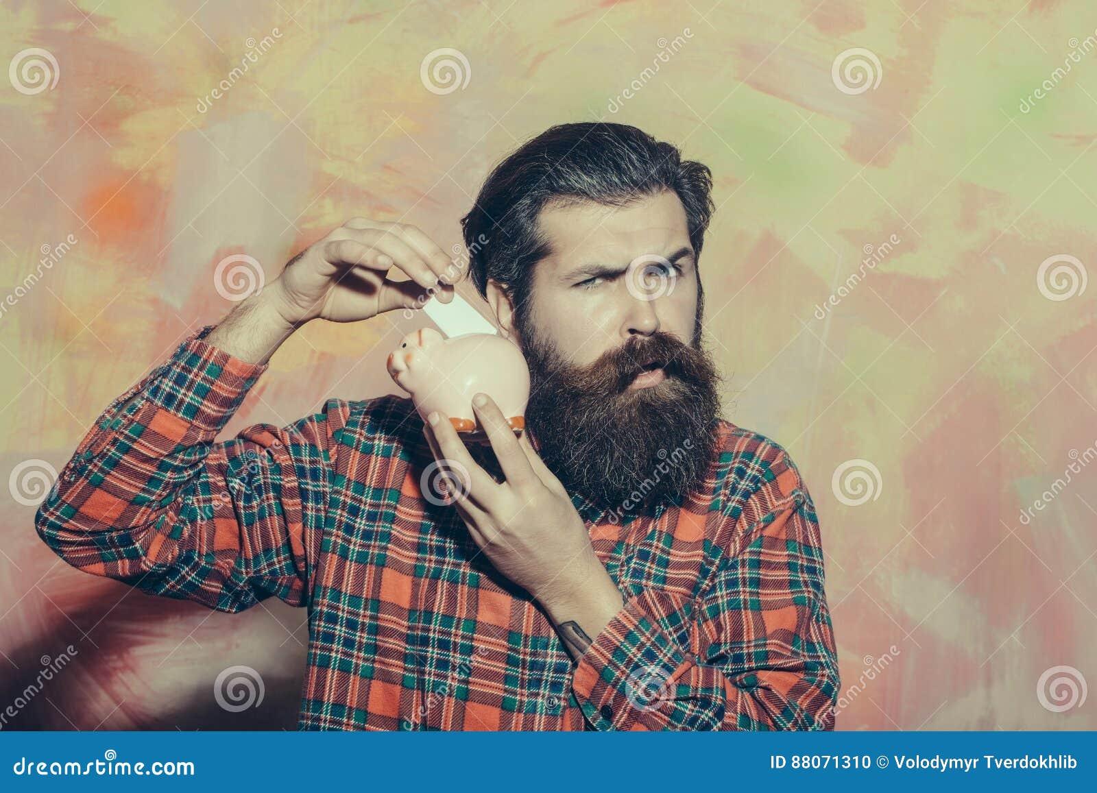 Homem farpado sério que põe a cédula no mealheiro cerâmico cor-de-rosa