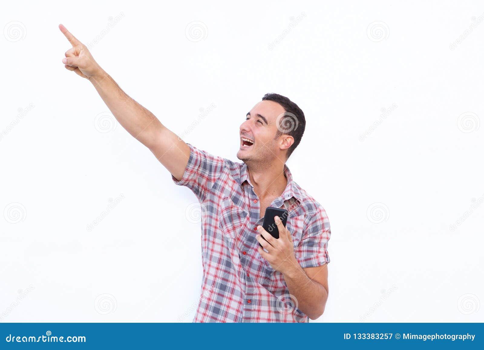 Homem feliz com telefone celular e apontar acima no fundo branco isolado