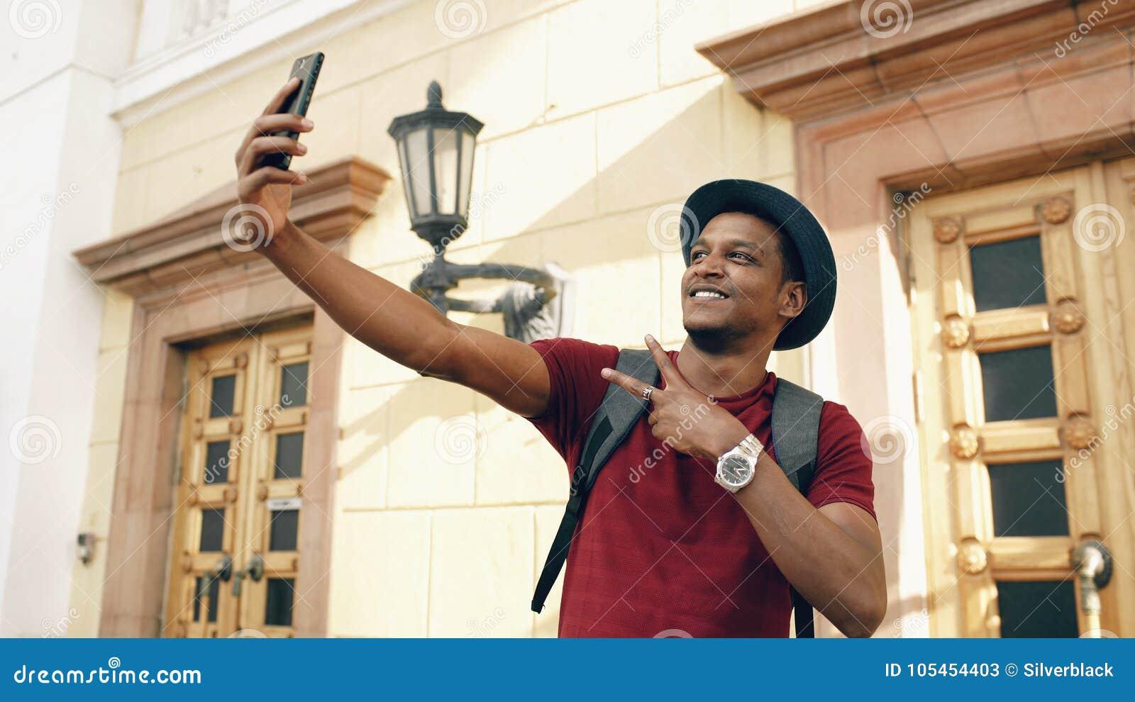 Homem feliz do turista da raça misturada que toma a foto do selfie em sua câmera do smartphone que está perto da construção famos