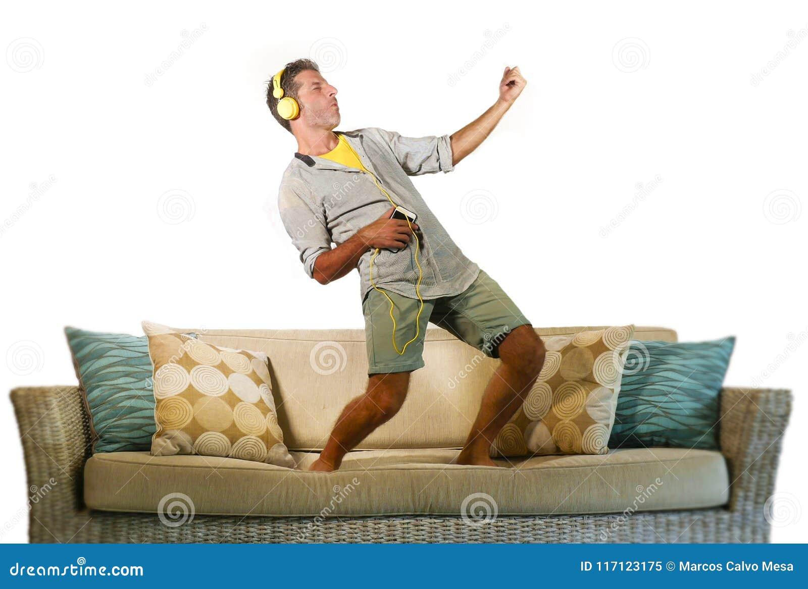 Homem feliz e entusiasmado novo que salta no sofá do sofá que escuta a música com o telefone celular e os fones de ouvido que jog