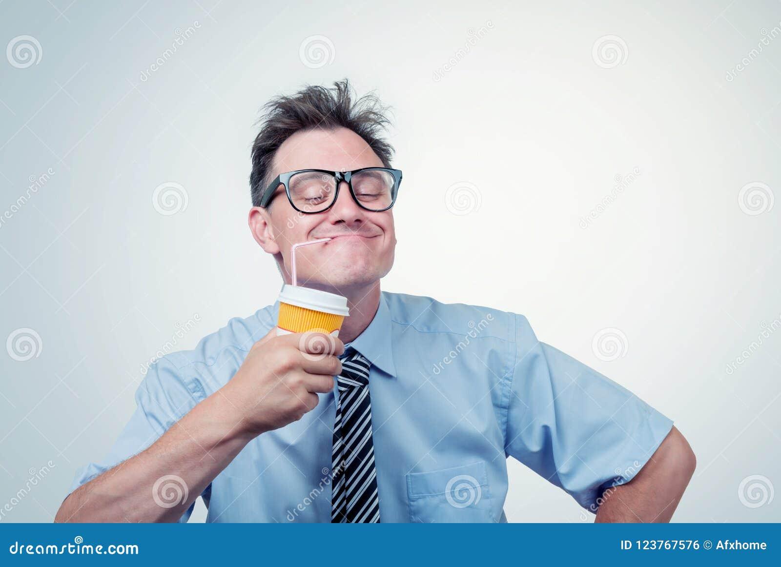 Homem feliz nos vidros que bebe de um copo de papel com uma palha, olhos fechados com prazer