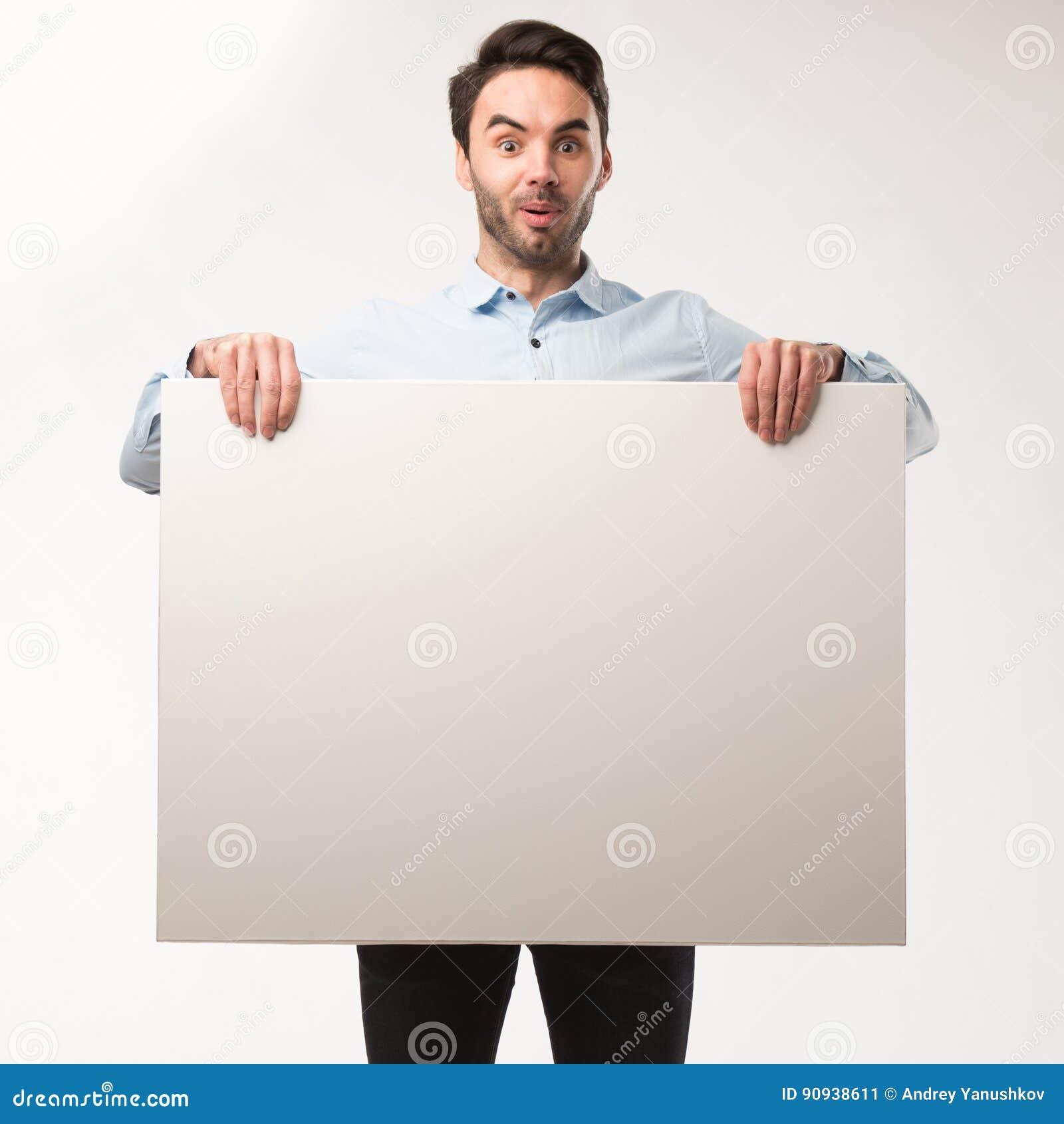 Homem feliz novo que mostra a apresentação, apontando no cartaz sobre o fundo cinzento