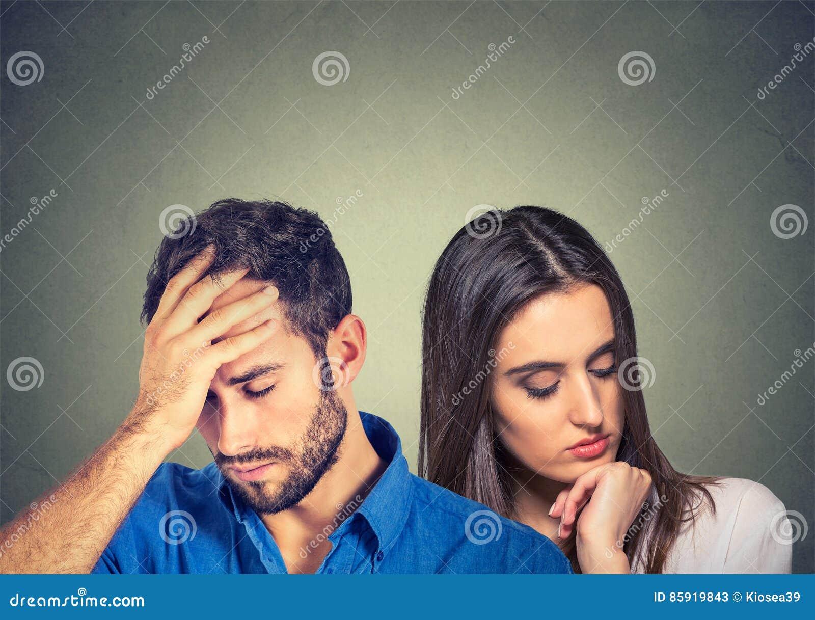 Homem forçado e mulher novos tristes dos pares que olham para baixo