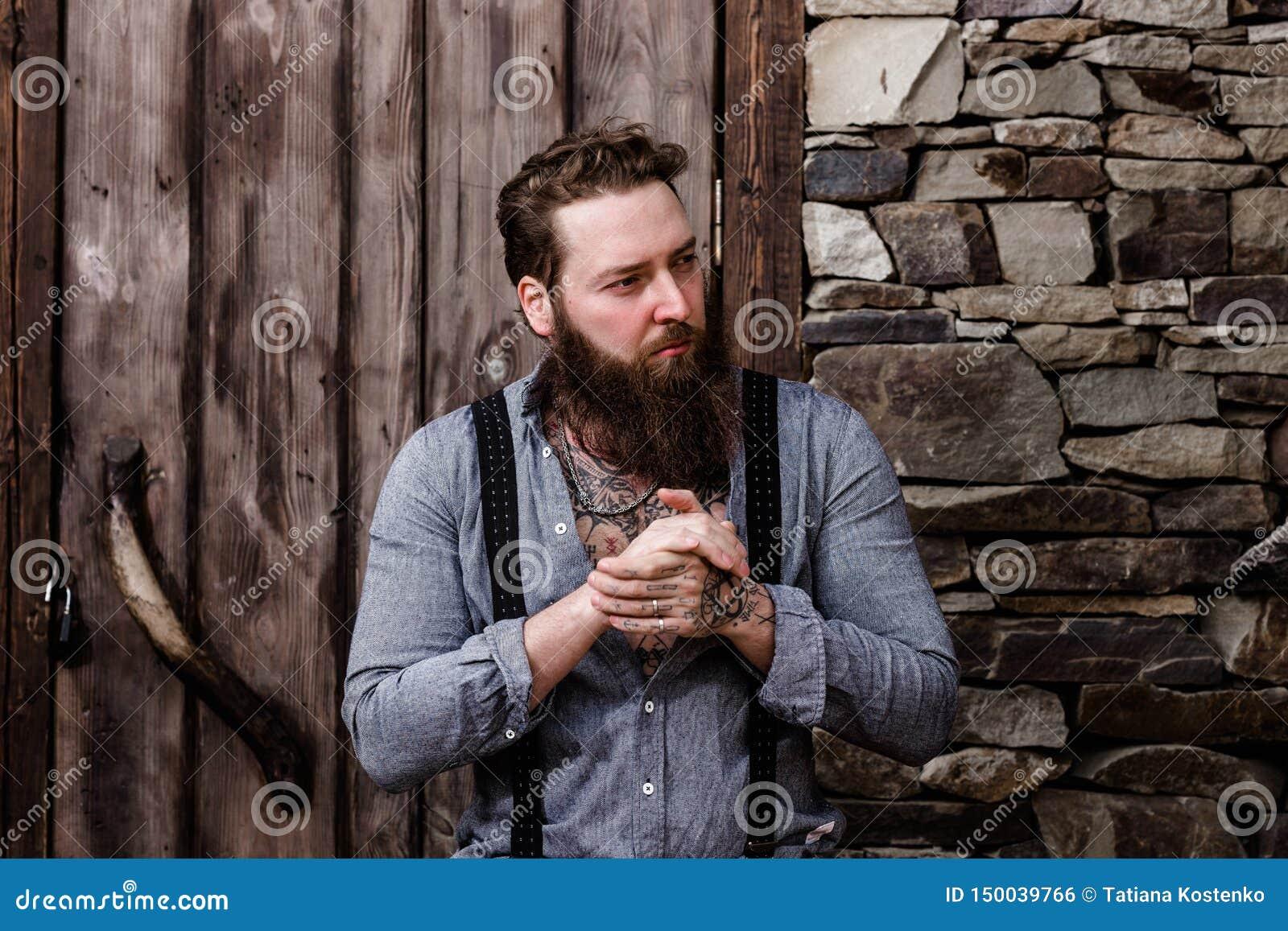 Homem forte brutal com uma barba e tatuagens em suas m?os vestidas em suportes ? moda da roupa ocasional no fundo de