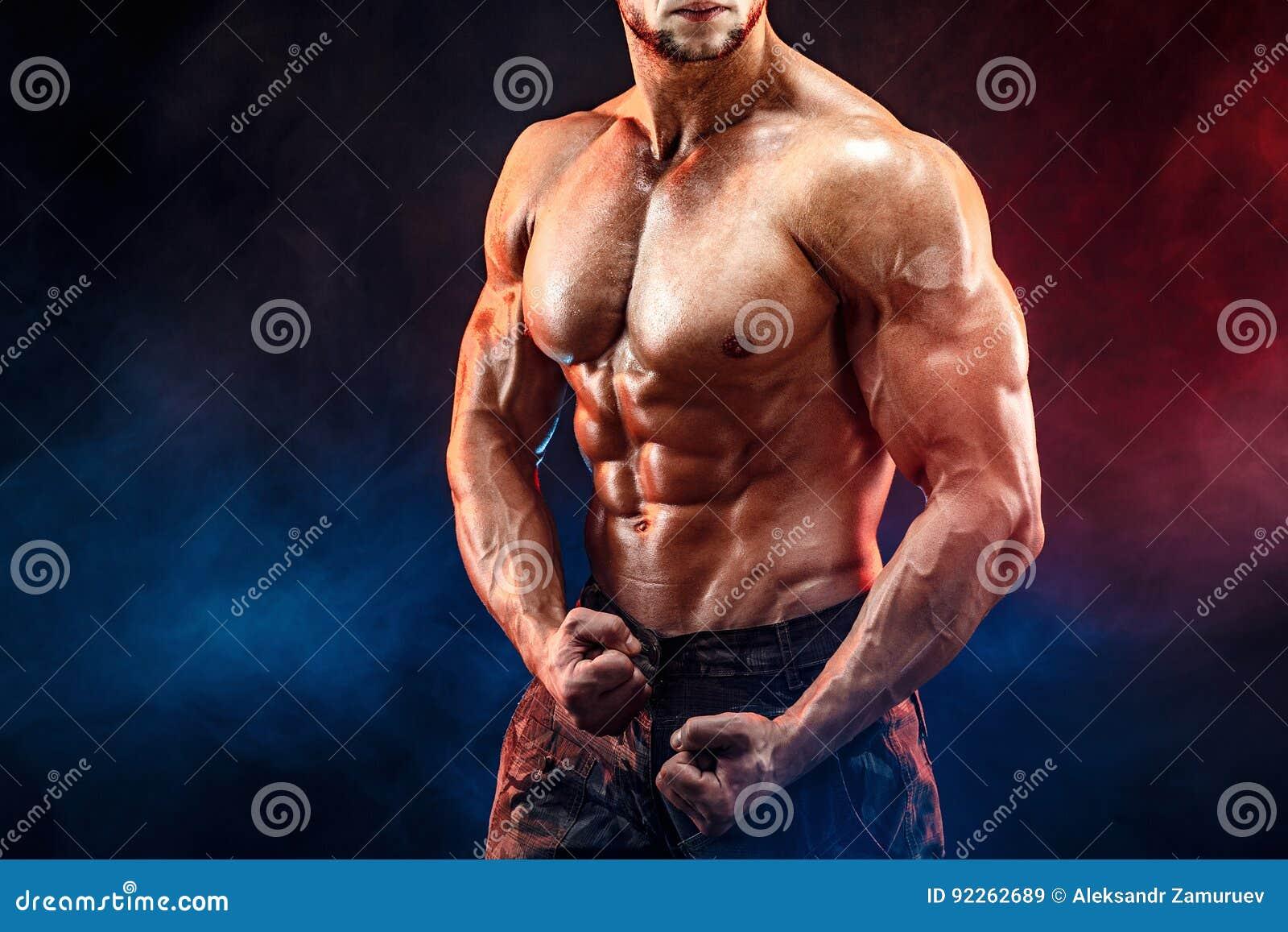 Homem forte do halterofilista em calças militares com Abs perfeitos, ombros, bíceps, tríceps, caixa
