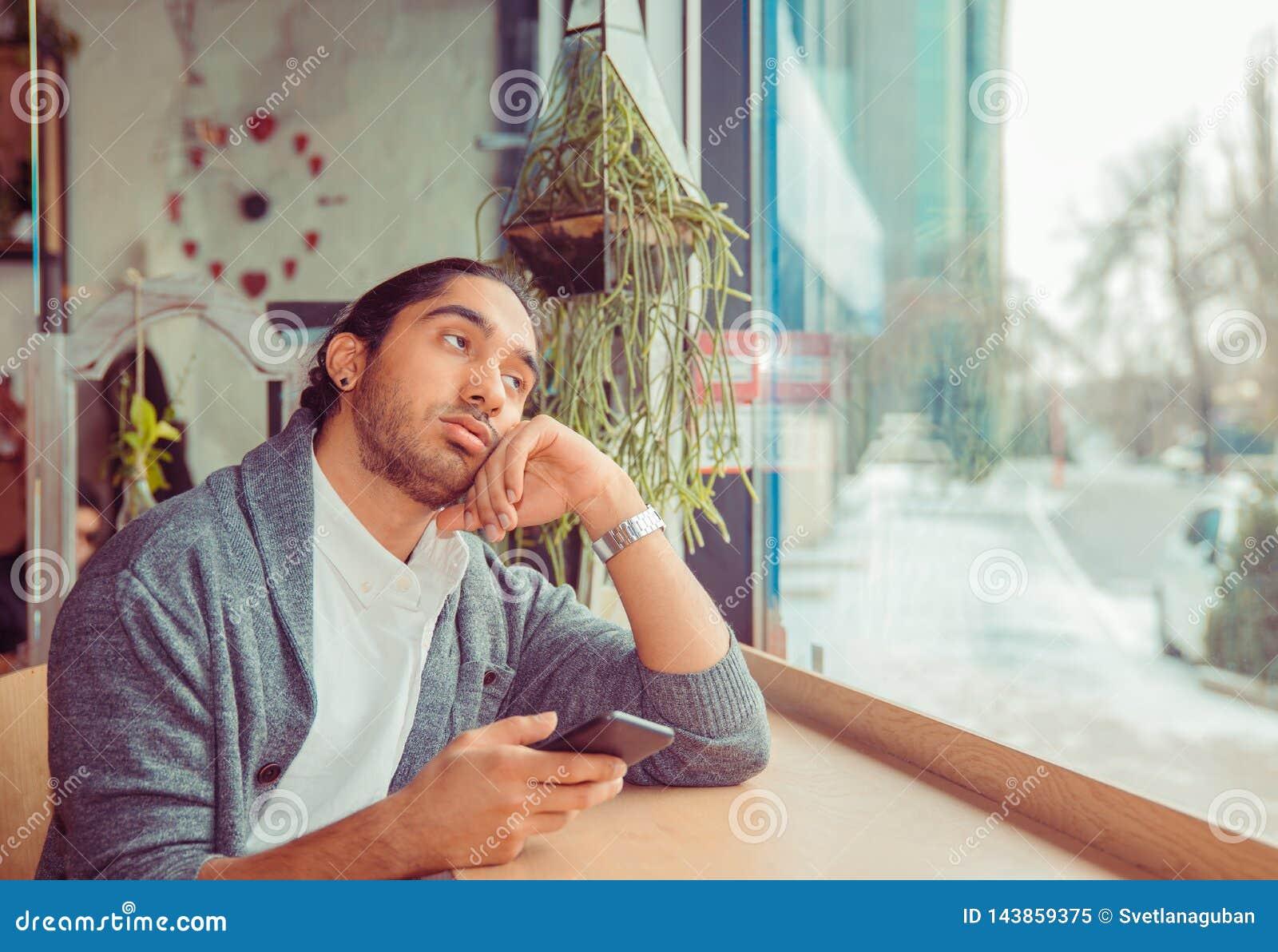 Homem furado que olha acima o telefone guardando cansado ? disposi??o