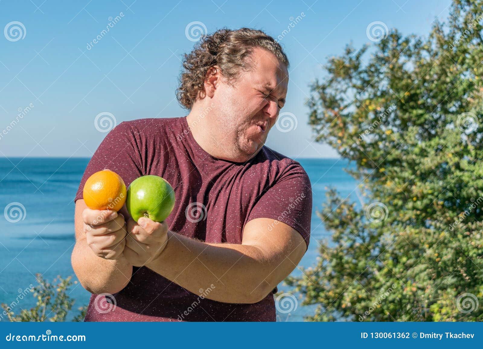 Homem gordo engraçado no oceano que come frutos Férias, perda de peso e comer saudável