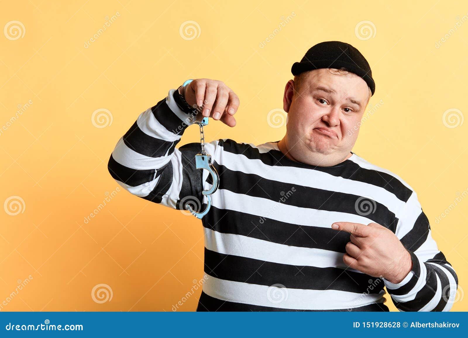 Homem gordo infeliz triste que aponta às algemas destravadas que penduram em sua mão