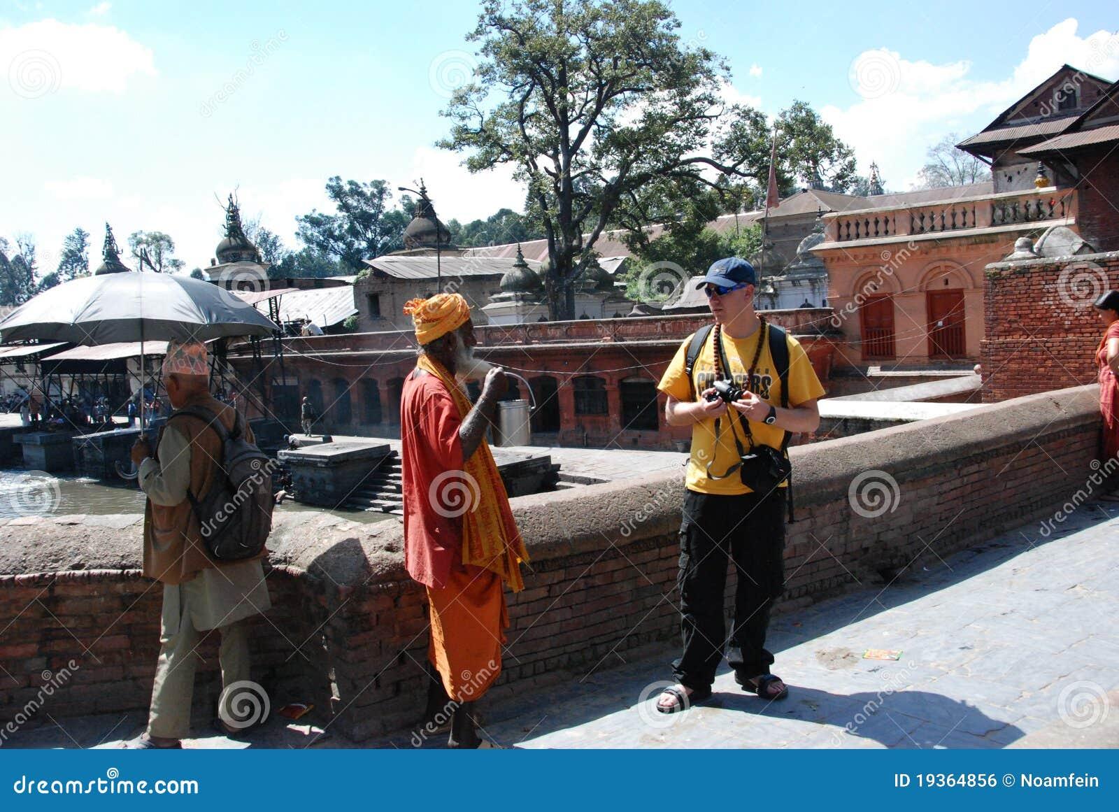 Homem Hindu local que fala a um turista
