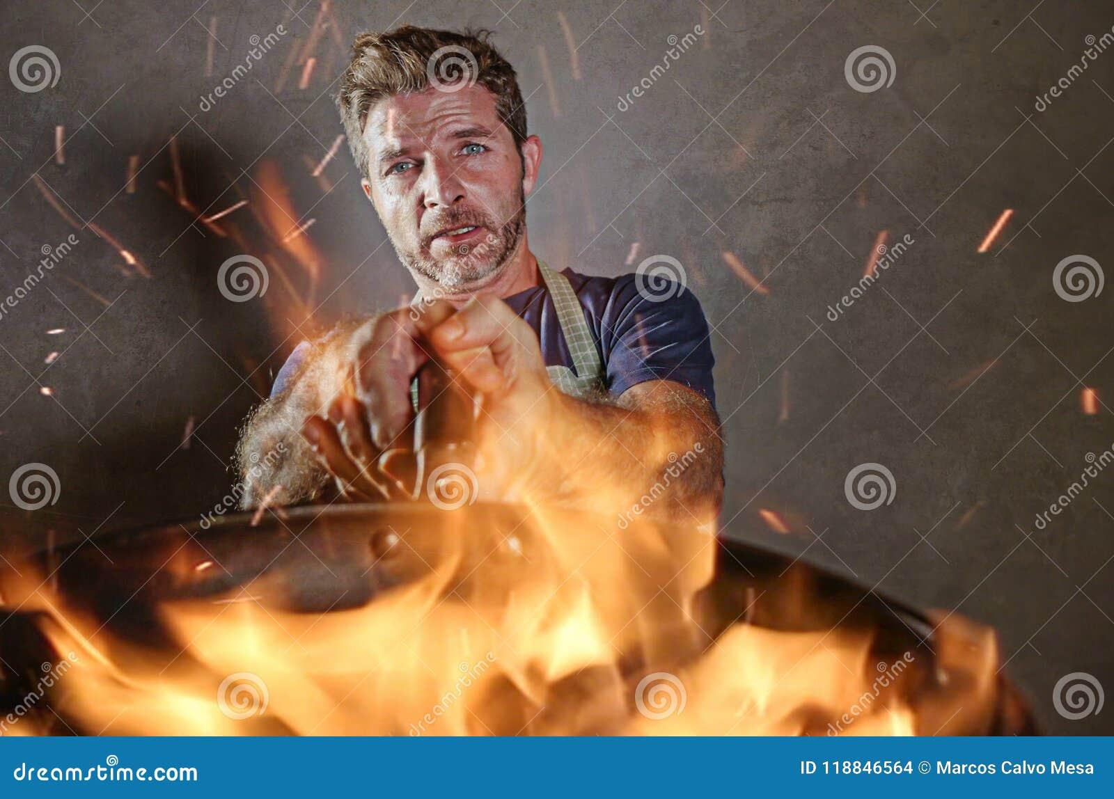 Homem home engraçado e desarrumado novo do cozinheiro com o avental em choque que guarda a bandeja no fogo que queima o alimento