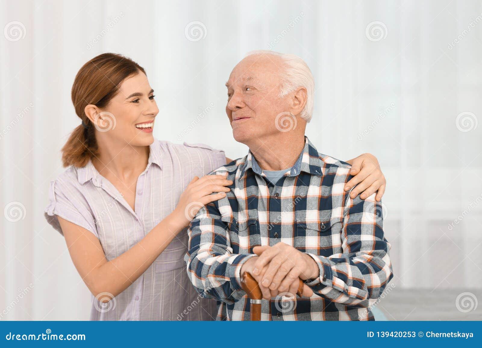 Homem idoso com cuidador fêmea