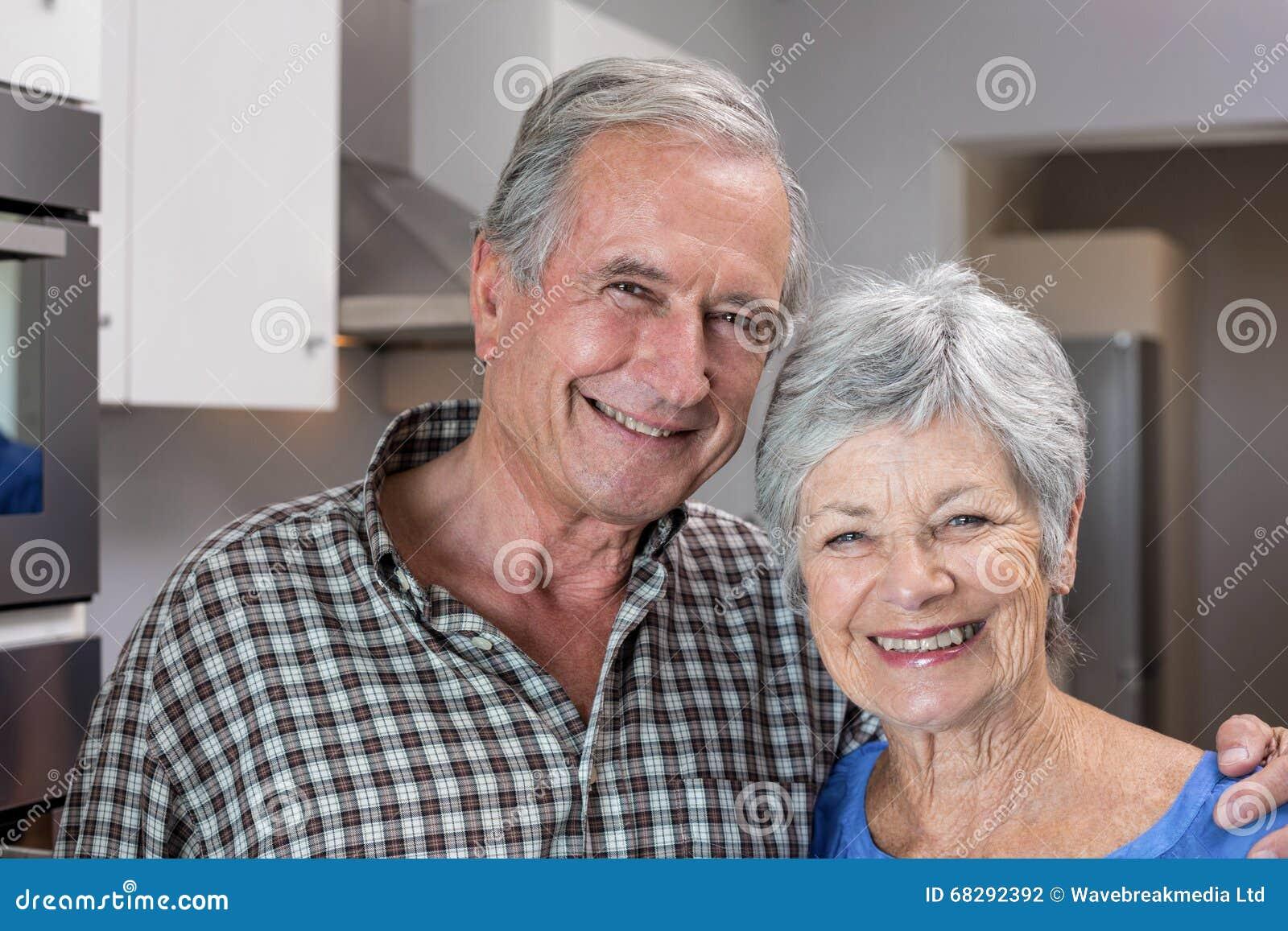 Homem idoso e mulher que estão na cozinha
