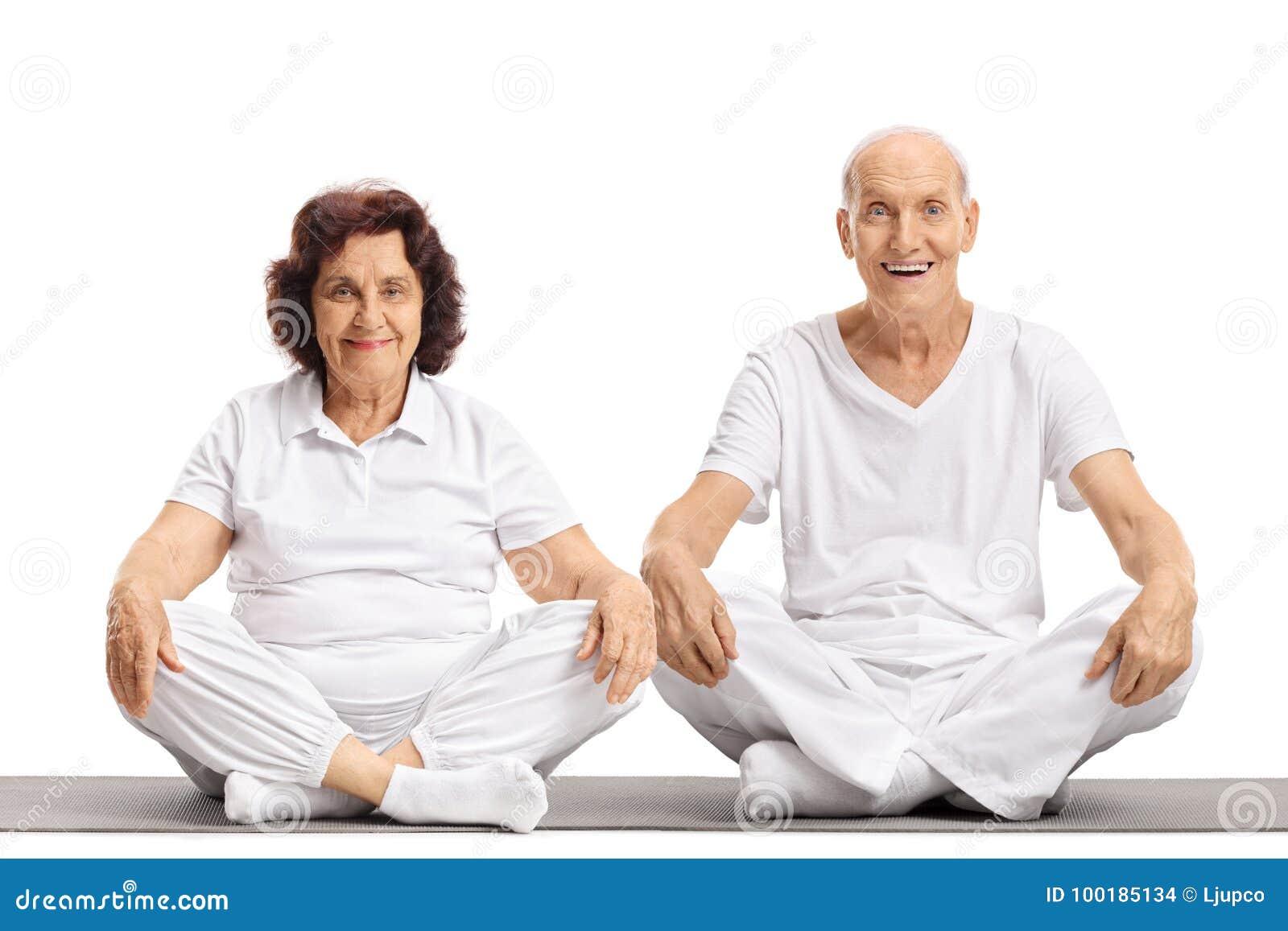 Homem idoso e uma mulher idosa que senta-se em uma esteira do exercício