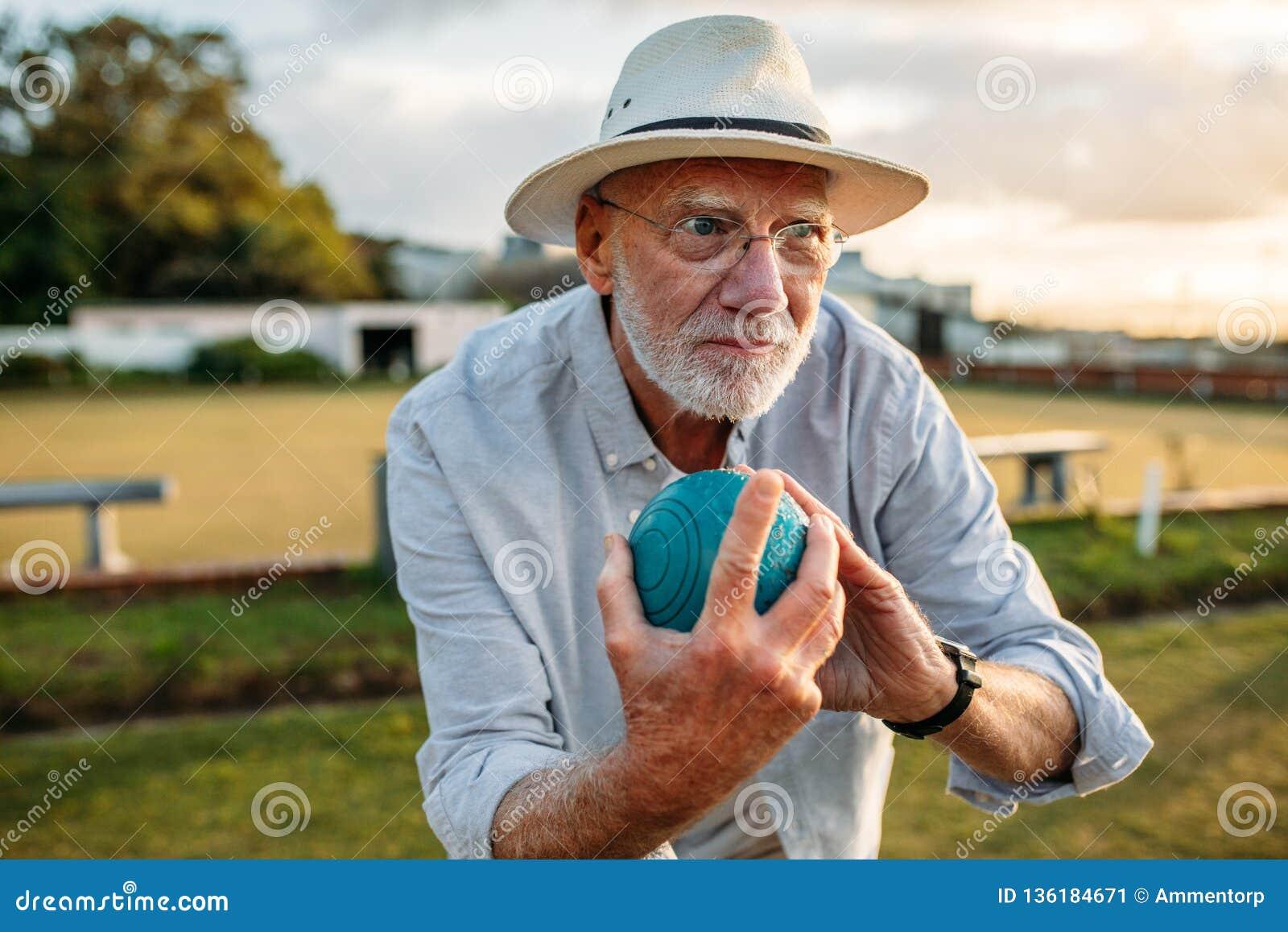 Homem idoso que joga um jogo dos boules