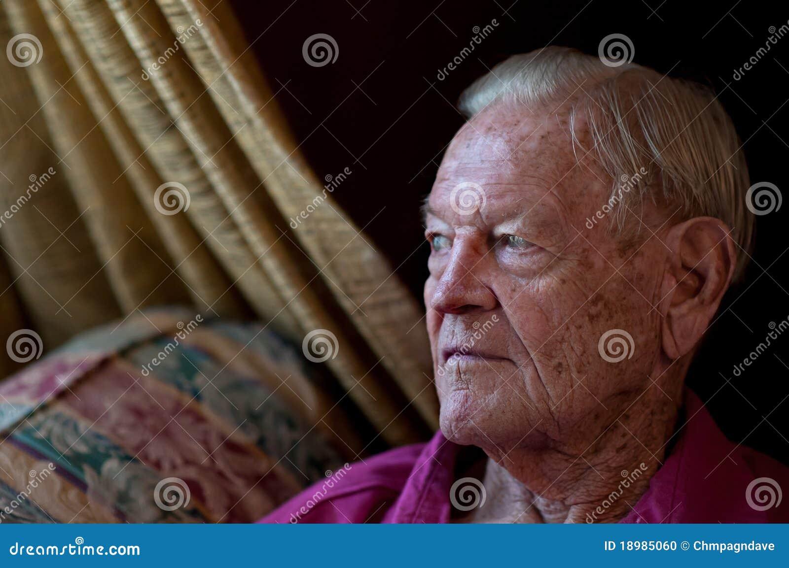 Homem idoso que senta-se pelo indicador na HOME