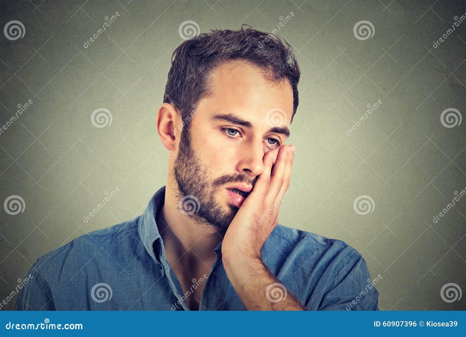 Homem infeliz desesperado no fundo cinzento da parede
