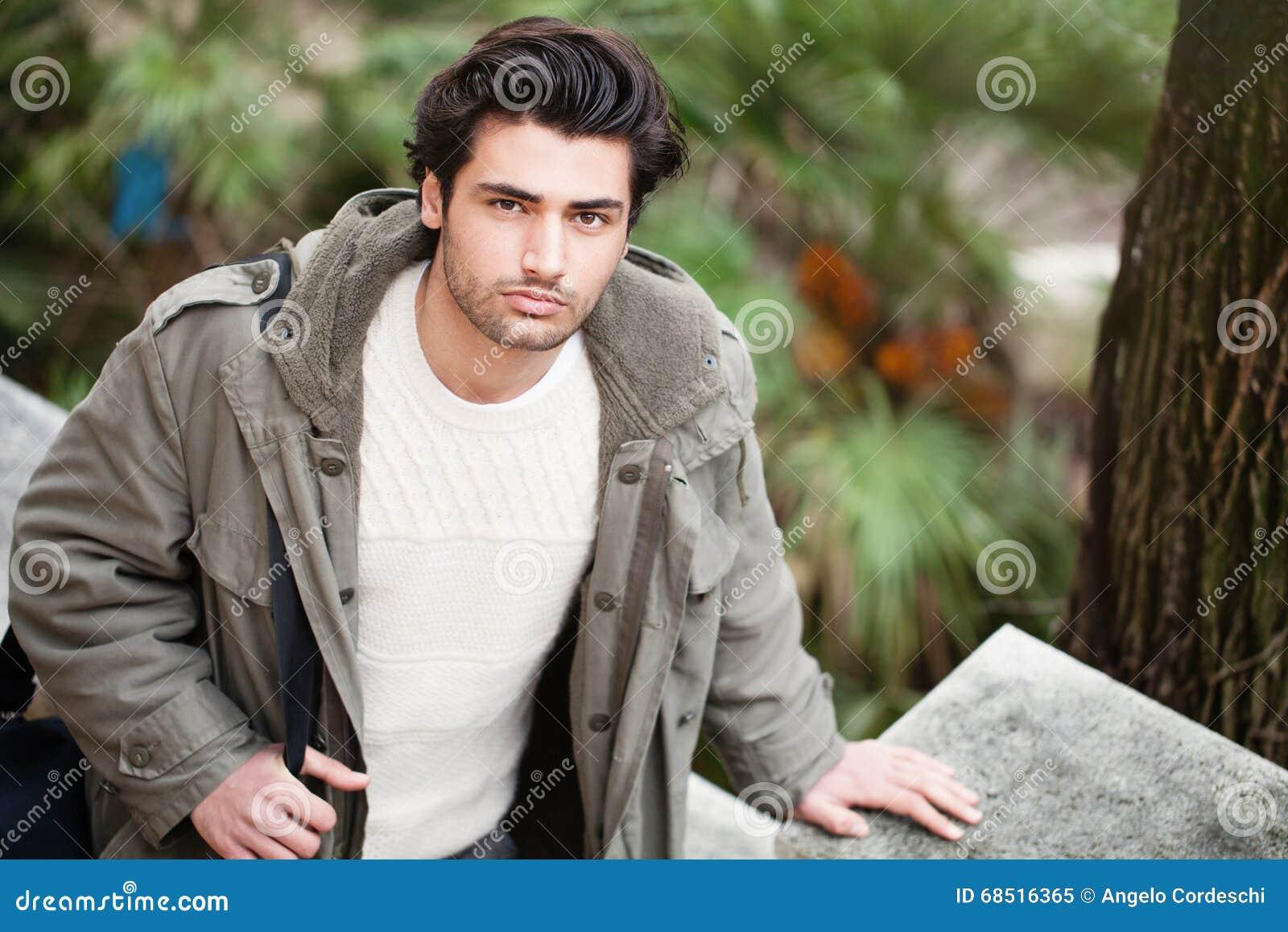 Homem italiano novo considerável, cabelo à moda e revestimento fora