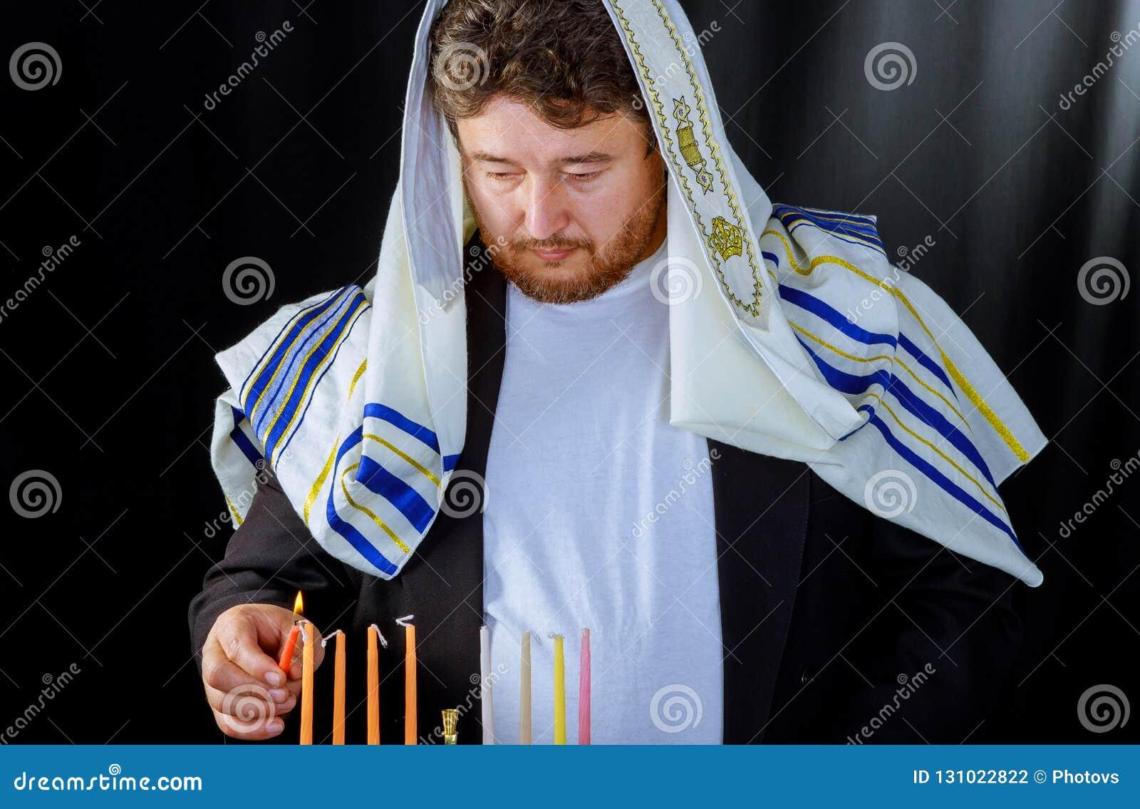 Homem judaico com a barba que ilumina velas para o hannukah
