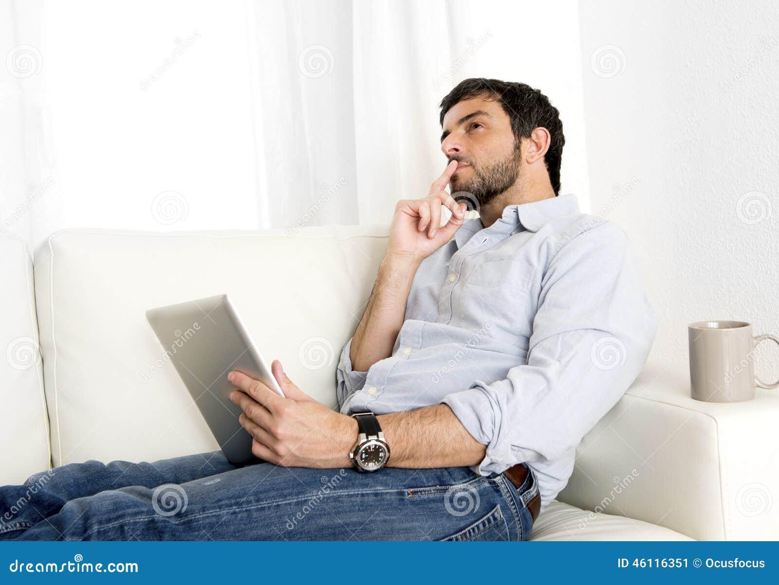 Homem latino-americano atrativo novo em casa no sofá branco usando a tabuleta ou a almofada digital