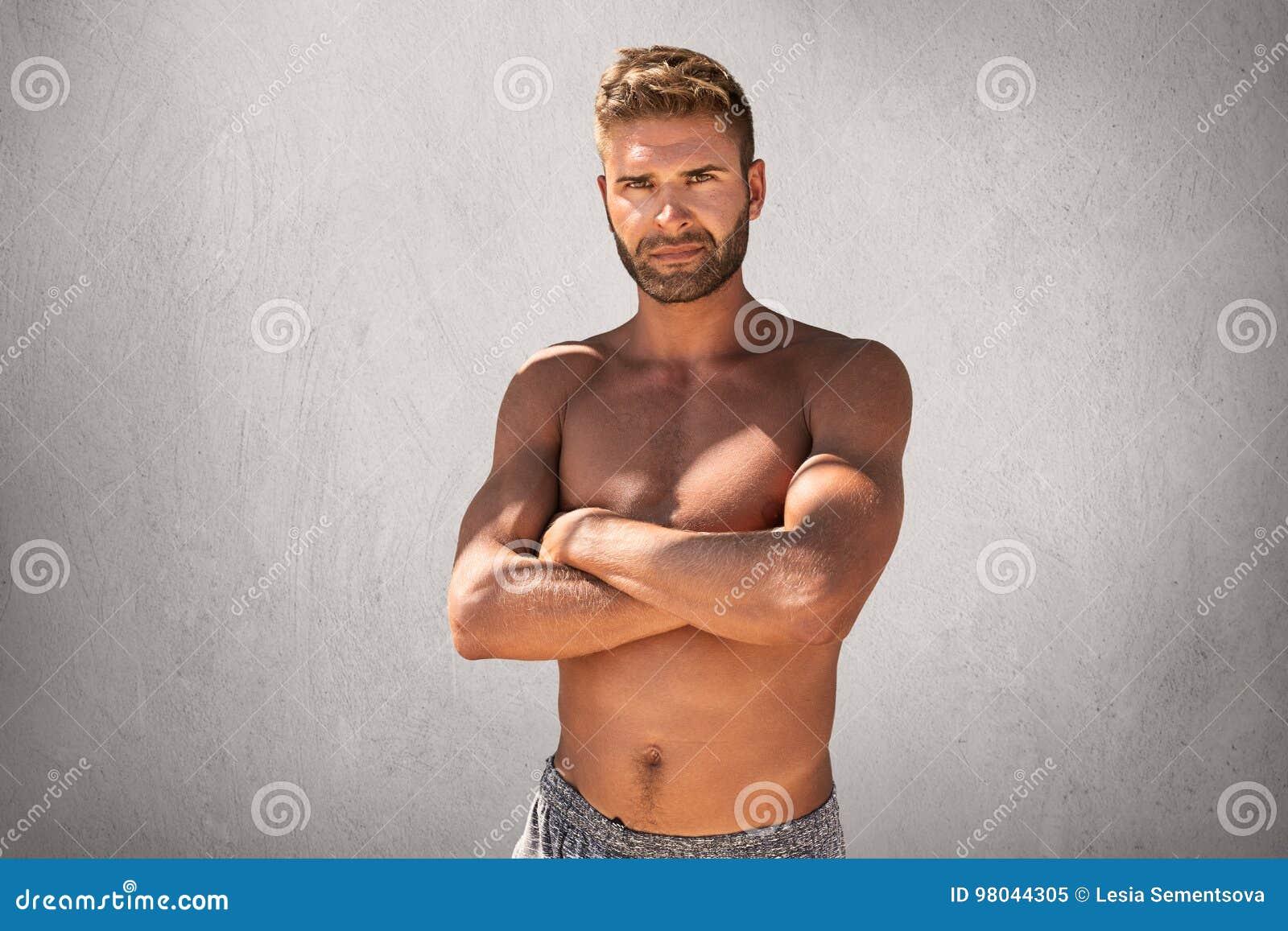 Homem macho considerável em topless com mãos cruzadas, sentindo suas força e confiança que levantam na câmera Indivíduo novo não