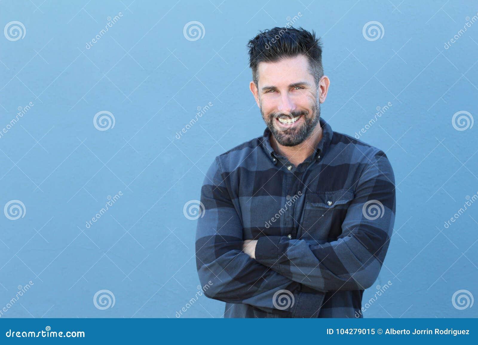 Homem maduro considerável que sorri e que ri ao cruzar seus braços com espaço da cópia