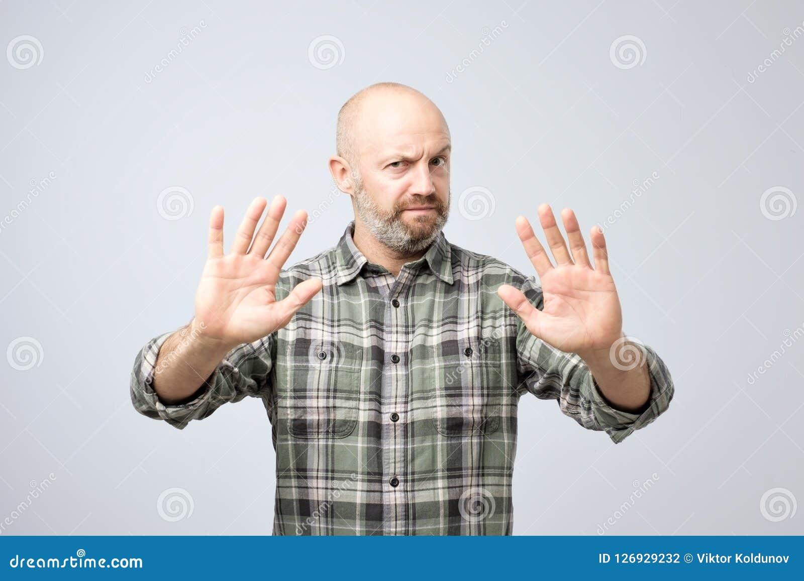 Homem maduro desagradado que recusa aceitar a ideia, esticando as mãos à câmera
