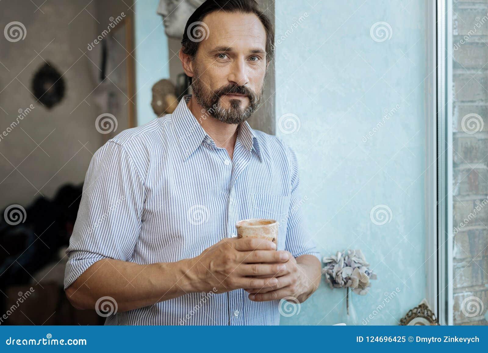 Homem maduro farpado que guarda o copo com chá quente