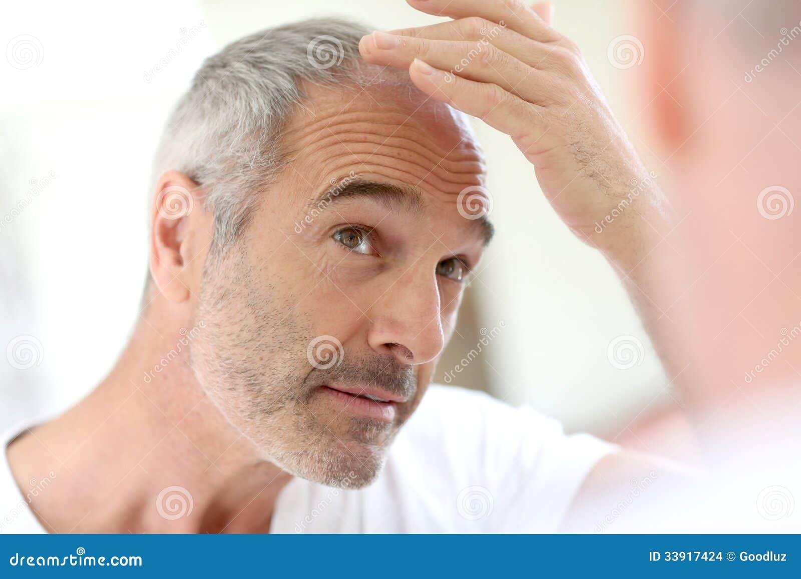 Homem maduro que olha a queda de cabelo