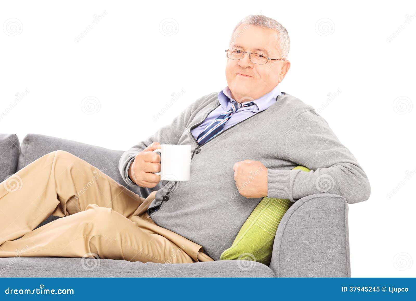 Homem maduro relaxado que coloca no sofá e no chá bebendo