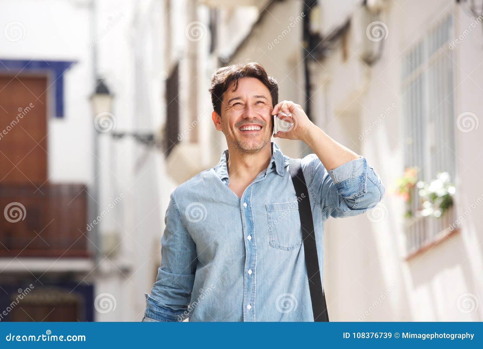 Homem mais idoso alegre que anda fora e que faz um telefonema