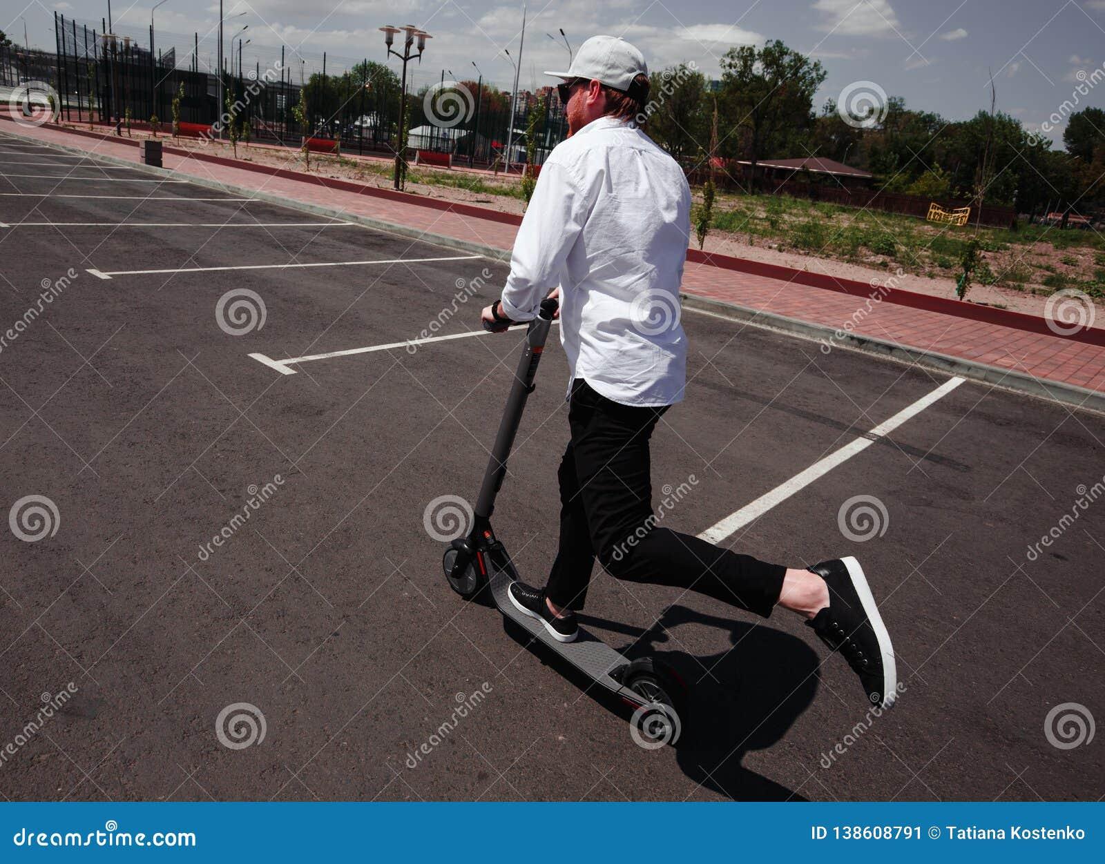Homem moderno no equipamento preto e branco à moda que monta o  trotinette  elétrico na cidade