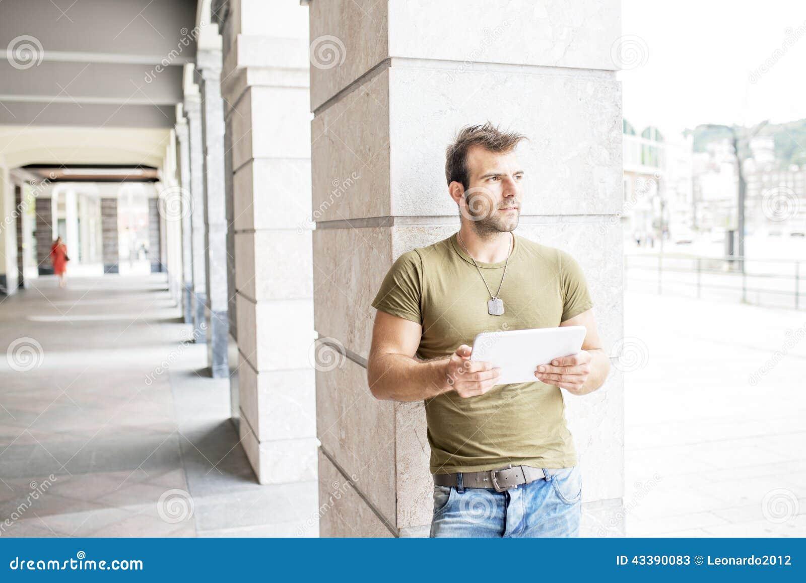 Homem moderno ocasional com o tablet pc na rua que olha afastado