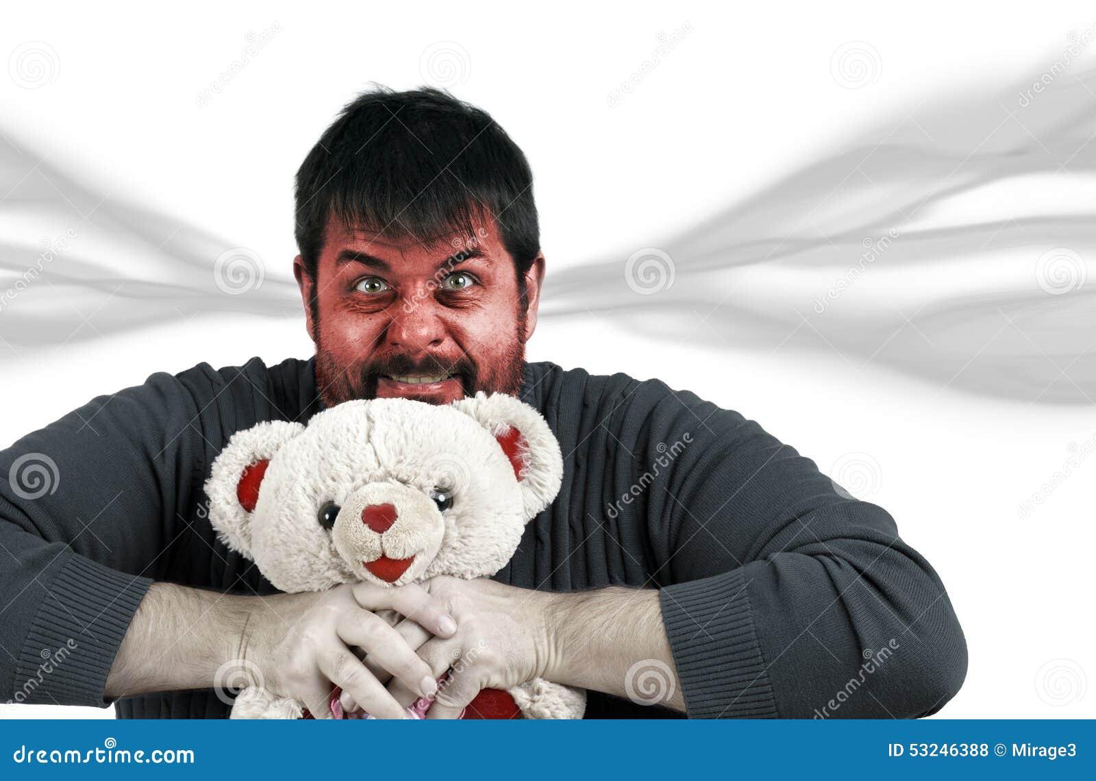 Homem muito irritado com urso de peluche