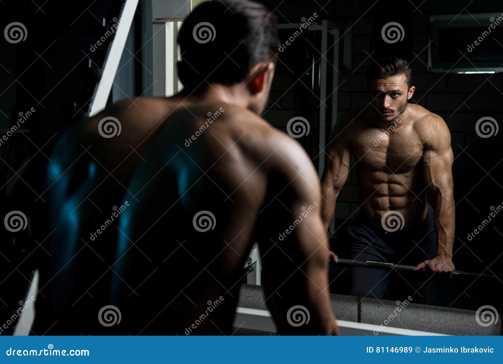 Homem muscular após o exercício que descansa no Gym