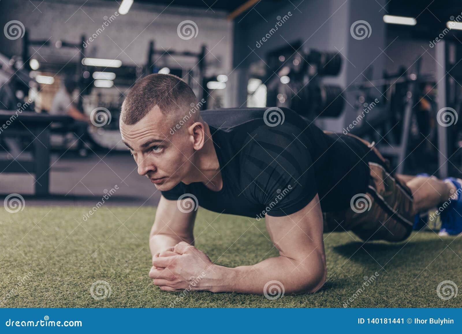 Homem muscular atlético que exercita no gym