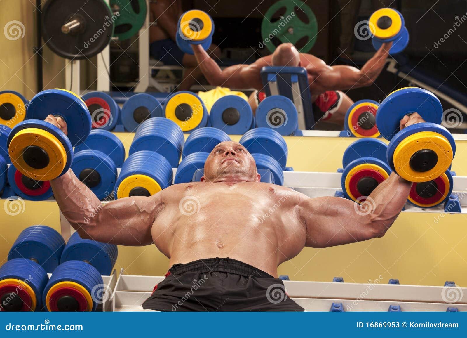 Homem muscular com pesos de uma barra na formação das mãos