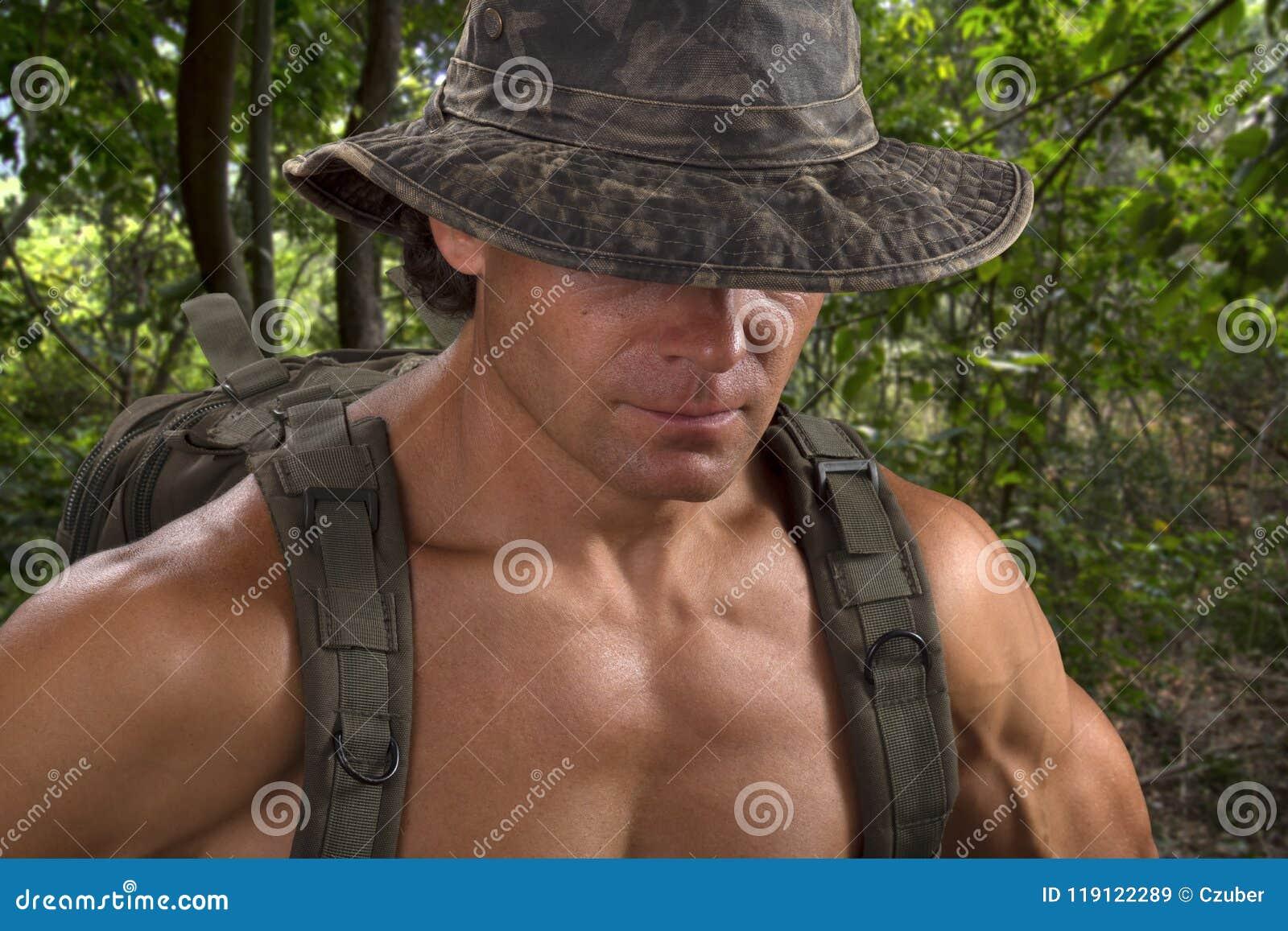Homem muscular da aventura no chapéu do camo que caminha na selva