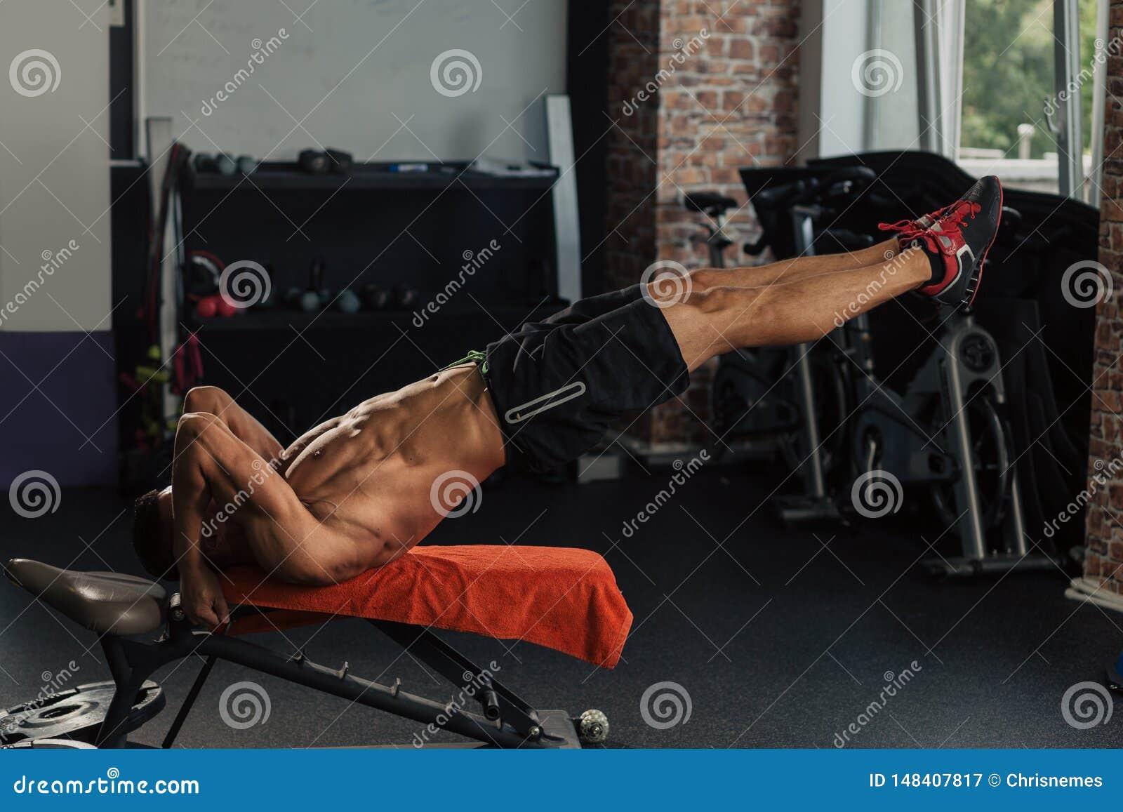 Homem muscular novo no gym que faz o exerc?cio