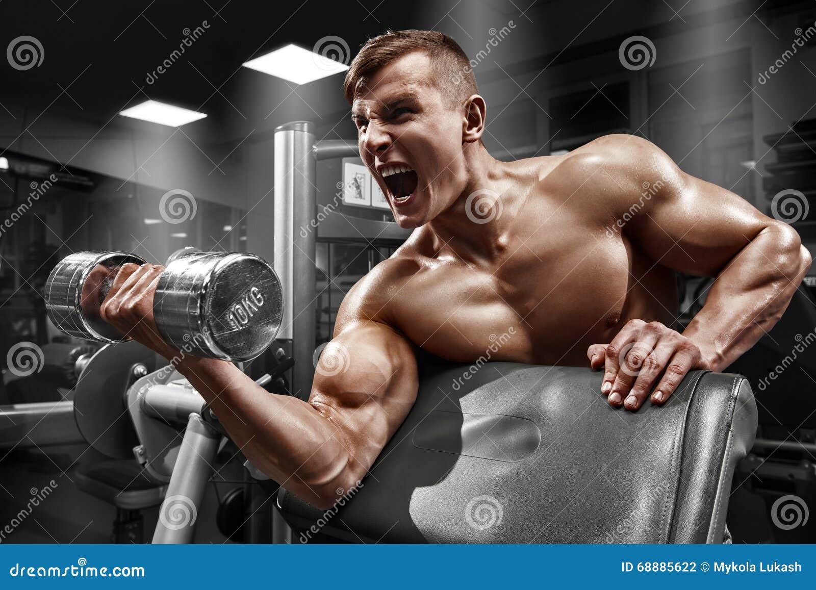 Homem muscular que dá certo no gym que faz exercícios com peso no bíceps, Abs despido masculino forte do torso