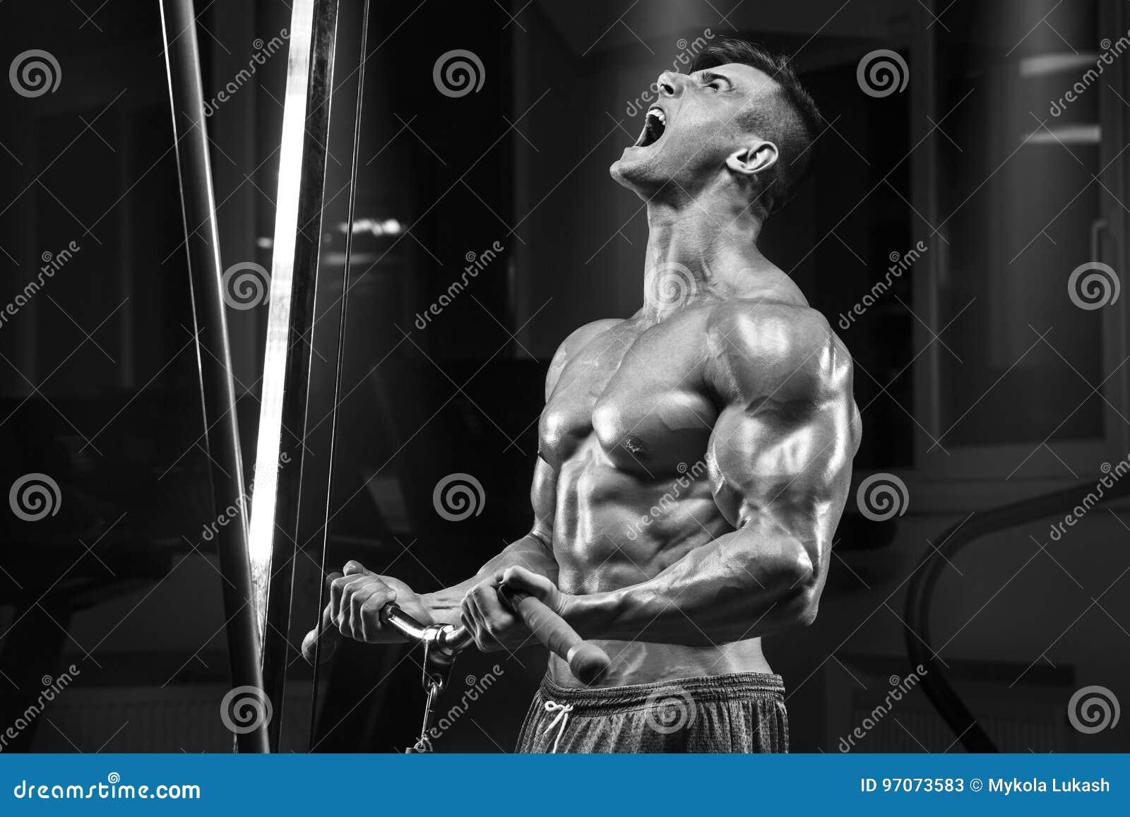 Homem muscular que dá certo no gym que faz o exercício, Abs masculino forte do torso