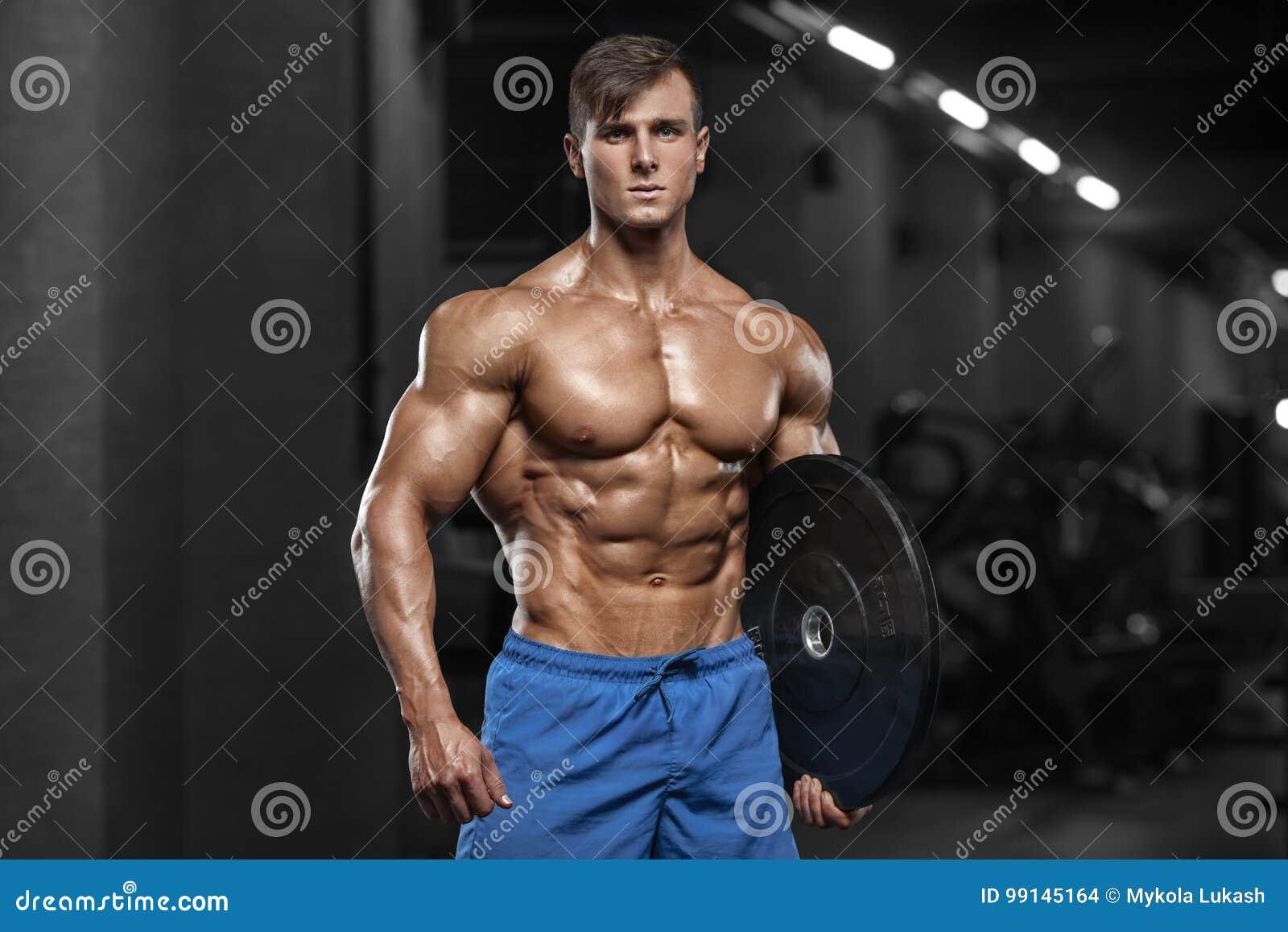 Homem muscular que mostra os músculos, levantando no gym Abs despido masculino forte do torso, dando certo