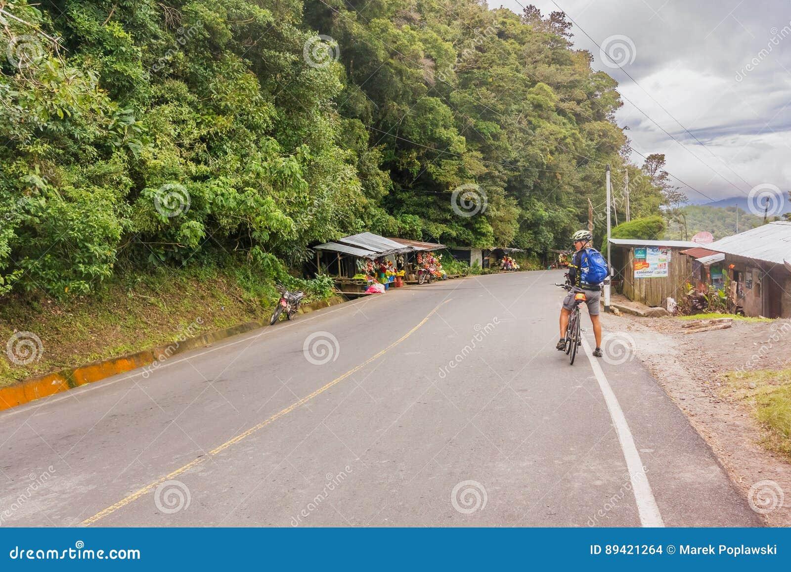 Homem, na bicicleta na estrada em montanhas de Nicarágua