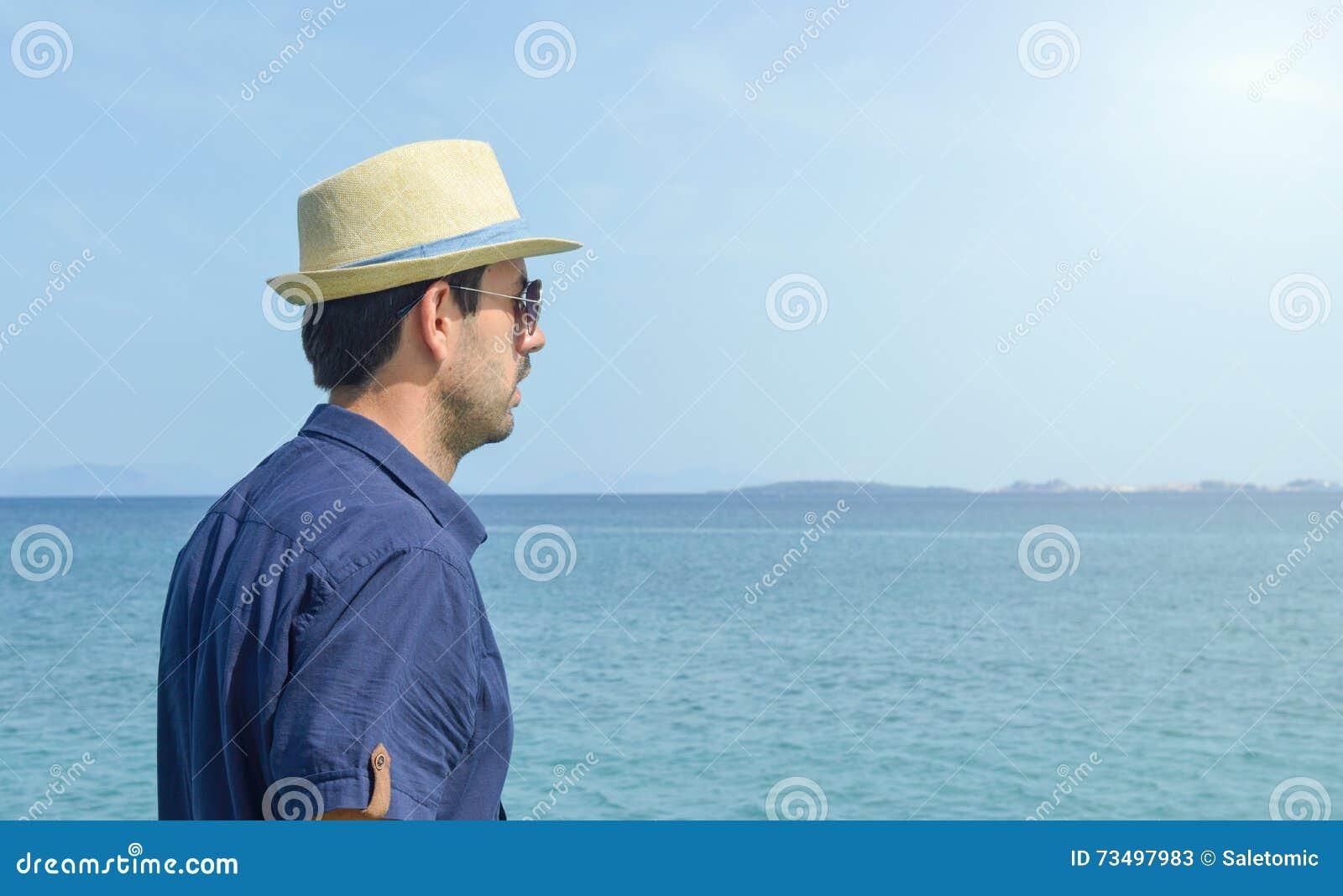 Homem na camisa azul que olha o horizonte