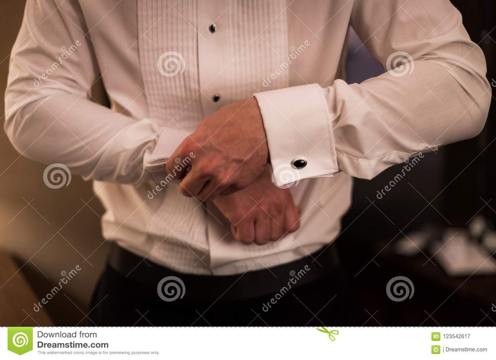 Homem na camisa de vestido que faz acima dos botão de punho
